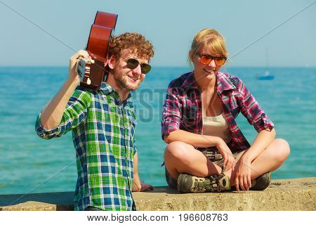 Young man playing guitar to his girlfriend outdoor by seaside - dating couple