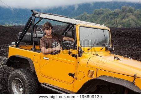 A curly-haired smiling man is sitting in the offroad yelow vehicle at the top of a valley with volcanic rock and mountains and watching to a viewer. Foggy landscape with forest in Bali, Indonesia