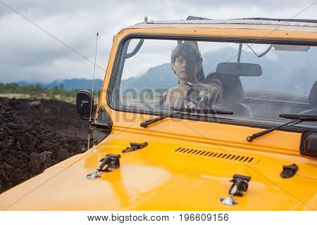 A curly-haired man is looking at the viewer in the offroad yelow vehicle at the top of a valley with volcanic rock and mountains. Foggy landscape with forest in Bali, Indonesia