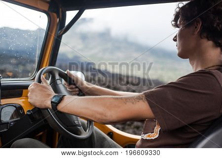 Close shot of a curly-haired tatooed man in brown T-shirt is sitting at the weel in the offroad yelow vehicle parked at top of a valley with volcanic rock and mountains in Bali, Indonesia