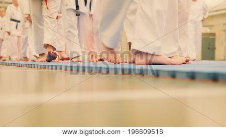 Karate training - group of karateka teenagers in kimono, close up