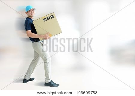 Deliveryman carrying a cardboard box on white gray background with copy space