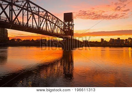 Scarlet sunrise with Roosevelt Island Bridge across the East Channel in New York USA. Bridge engineering design highlighted by pastel colors of the sky at sunrise.