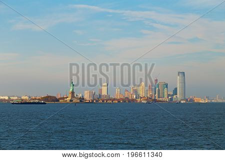 Lower Manhattan panorama and statue of Liberty in New York at dusk. Urban landscape of USA largest city from the river.