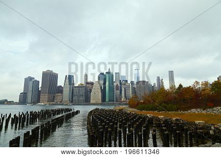 Lower Manhattan panorama on a cloudy morning in autumn New York USA. Distant view of New York landmarks and park in fall bright colors.