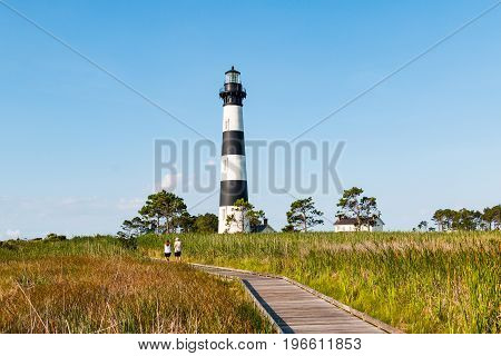 NAGS HEAD, NORTH CAROLINA - JULY 14, 2017:  People walk on the wooden boardwalk through marshland near the historic Bodie Island lighthouse on the Outer Banks.