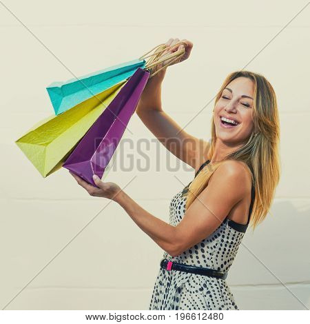 Excited cheerful woman showing her shopping bags. image with toning