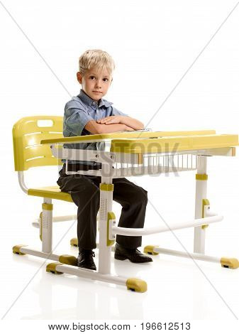 Full portrait of cute schoolboy sitting at the desk with folded hands