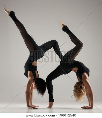 Portrait of two fit acrobatic women posing on light gray background