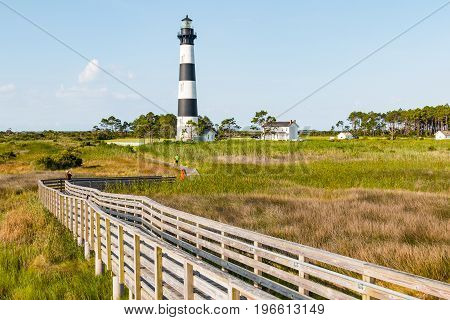 NAGS HEAD, NORTH CAROLINA - JULY 14, 2017:  People tour the grounds of the Bodie Island lighthouse on the wooden walkway through the surrounding marshlands.
