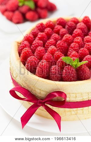 Birthday spongecake with raspberries decorated red ribbon and bow on a white background
