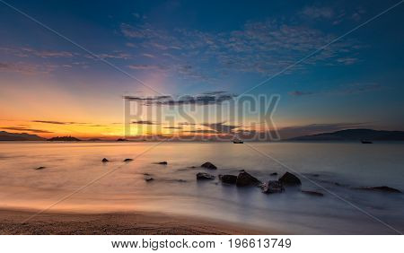 Nha Trang Vietnam sunrise with a cloudy blue orange sky over the ocean long exposure.