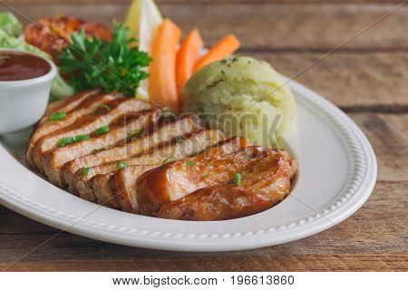 Barbecue pork steak slices on white plate. Delicious pork steak for lunch or dinner on wood table. Moist and soft homemade pork barbecue served with mash potato barbecue sauce and vegetable. Slices pork steak barbecue ready to served.