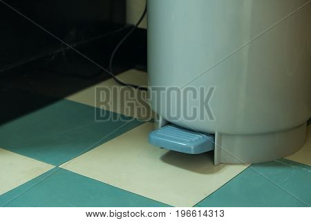 Gray Plastic Trash Can With Pedal On Green Floor Pattern.