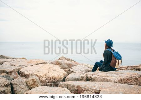 Girl traveler in a hat with a backpack next to the sea looking into the distance. Travel, hiking, freedom.