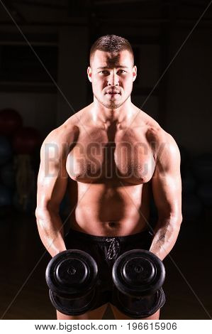 Handsome power athletic guy bodybuilder doing exercises with dumbbell. Fitness muscular body on dark background.