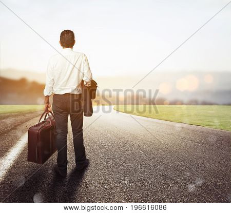 Man walks on a road with his suitcase to reach the goal