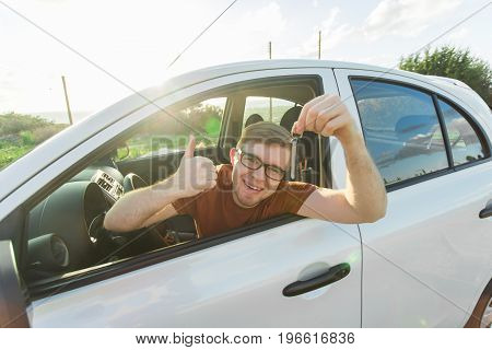 Young man smiling and holding key in his car.