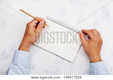 Lefty writes in clean notebook on white table top view. International Lefthanders Day.