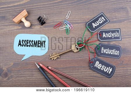 Assessment Concept. The key to success on a wooden office desk.
