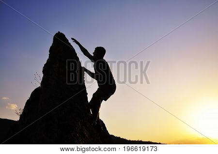 Men trying to climb on the top of the steep rock. Going to the top. Extreme climbing