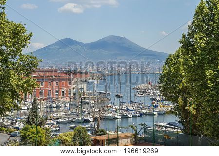 magnificent view of Mount Vesuvius and Gulf of Naples through the picturesque marina, in good weather, Naples, Italy