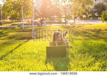 Young woman using laptop in the park lying on the green grass. Leisure time activity concept.