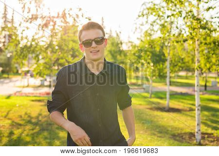 Confident handsome guy in sunglasses in a park. Men's beauty, fashion. Outdoor portrait