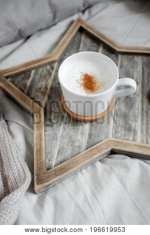 A cup of coffee on a Scandinavian wooden star-shaped tray in a cozy bed