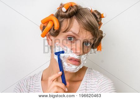 Young Woman Shaves Her Face With Foam And Razor