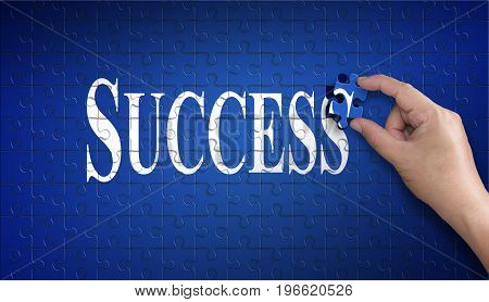 Success word on Jigsaw puzzle - business concept. Man hand holding a blue puzzle to complete the word Success divided over them concept of the solution to a problem challenge plan and strategy.