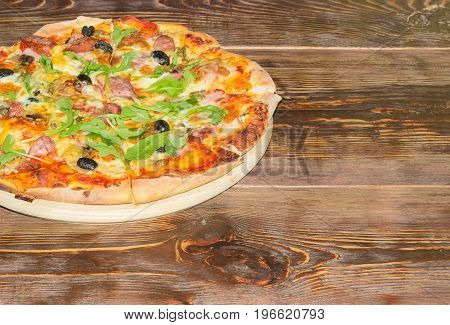 Fragment of the cooked round pizza with sausages mushrooms olives and arugula on the old wooden table