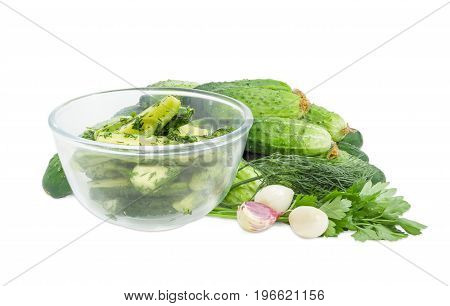 Lightly salted cucumbers in the glass bowl on a background of a pile of the freshly picked out cucumbers parsley dill and garlic on a white background