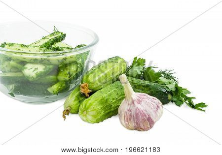 Fragment of the glass bowl with lightly salted cucumbers and several freshly picked out cucumbers parsley dill and garlic beside on a white background