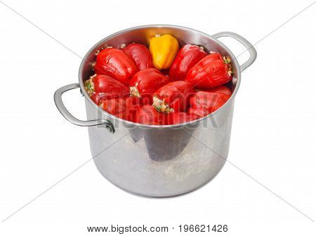 Cooked stuffed red and yellow bell peppers in the large stainless steel saucepot on a light background