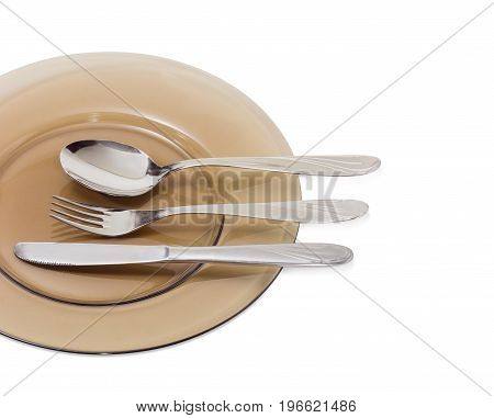 Fragment of the dark glass dish and eating utensils consisting of spoon fork and knife made from stainless steel on it closeup on a light background