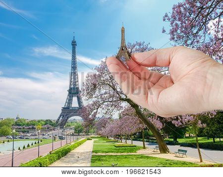 View of the Eiffel Tower from park and Trocadero Square with small metal Eiffel Tower model in man's hand in a foreground in Paris