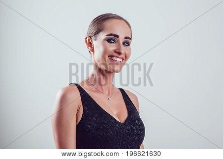 Beautiful woman in black night fashion dress posing on a gray background.