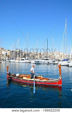 VITTORIOSA, MALTA - MARCH 31, 2017 - Man steering a traditional Maltese Dghajsa water taxi in the harbour with views towards Senglea waterfront Vittoriosa Malta Europe, March 31, 2017.