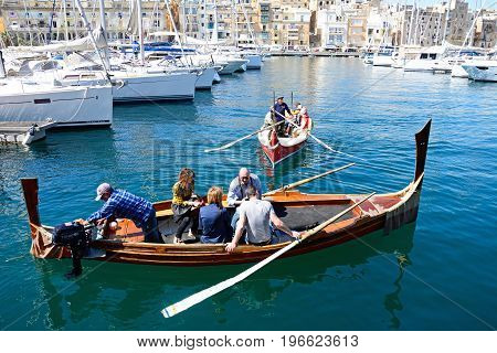 VITTORIOSA, MALTA - MARCH 31, 2017 - Passengers on board traditional Maltese Dghajsa water taxis in the harbour with views towards Senglea waterfront Vittoriosa Malta Europe, March 31, 2017.