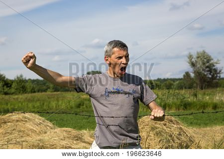 A screaming man clinging to a barbed wire and a clenching fist