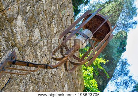 one steel lamp on an ancient stone wall