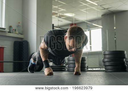 Sportsman Wearing Black Shorts And T-shirt Doing Push-ups On Fists In Gym.