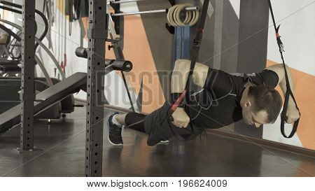 Attractive Man Does Crossfit Push Ups With Fitness Straps In The Gym