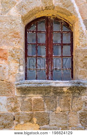 old window closeup on an ancient stone wall