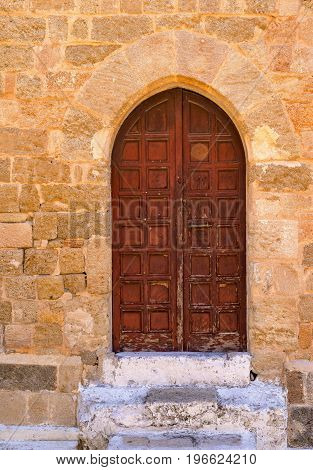 old wooden door on an ancient stone wall