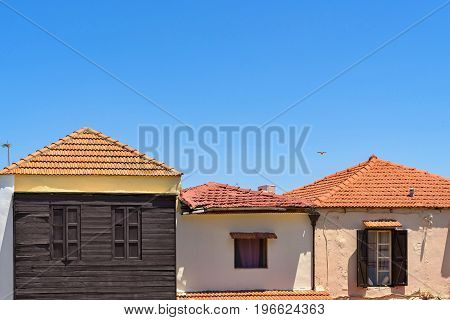 facades of old small houses close up against the background of the clear and empty sky monochrome tone