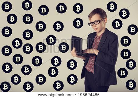 Portrait Of Business Child In A Suit And Glasses Earning Virtual Money In Internet. Young Miner On B