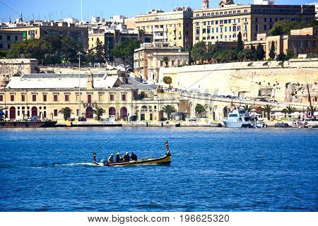 VALLETTA, MALTA - MARCH 31, 2017 - Passengers on board a traditional Maltese Dghajsa water taxi in the grand harbour with views towards Valletta Vittoriosa Malta Europe, March 31, 2017.