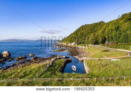 The eastern coast of Northern Ireland and Antrim Coastal Road a.k.a. Causeway Coastal Route. A boat houses and fences. Aerial view at sunrise